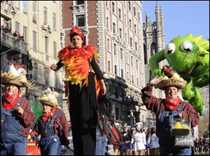 Costumed characters and a marching band precede the Kermit The Frog balloon on New York's Central Park West during the 86th annual Macy's Thanksgiving Day Parade.
