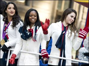 US gymastics team members, from right, McKayla Maroney, Gabby Douglas and Aly Raisman ride a float in the Macy's Thanksgiving Day Parade in New York.
