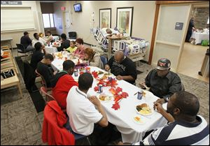 Anthony Taylor, in his hospital bed, and his family gather for their Thanksgiving Day meal at the University of Toledo Medical Center.