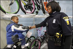 "Officer Katrina Welch-Bills helped Javarious Allen find a bicycle while participating in the first ""12 Kids of Christmas"" program in 2009."