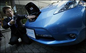 A Nissan employee demonstrates the electric recharge plug-in process for the company's latest Leaf. Plans for U.S. sales of the vehicle have not been detailed.