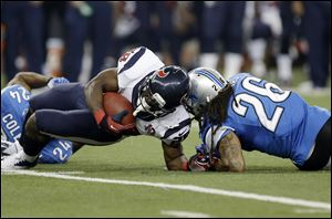 Houston Texans running back Justin Forsett is hit by Detroit Lions free safety Louis Delmas (26) during the third quarter today at Ford Field in Detroit. Forsett scored an 81-yard touchdown on the controversial paly.
