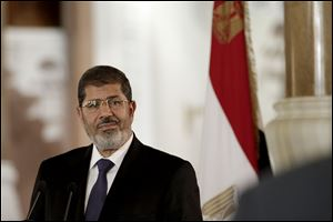 Egyptian President Mohammed Morsi, right, swears in his new Prosecutor General, Talaat Abdullah, left, in Cairo, Egypt, Thursday. Egypt's president on Thursday issued constitutional amendments granting himself far-reaching powers and ordering the retrial of leaders of Hosni Mubarak's regime for the killing of protesters in last year's uprising. Morsi also on Thursday fired the country's top prosecutor by decreeing with immediate effect that he could only stay in office for four years and replacing him with Talaat Abdullah. Morsi fired Abdel-Maguid Mahmoud for the first time in October, but had to rescind his decision when he found that the powers of his office do not empower him to do so.