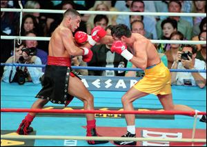 Hector Camacho, left, fights Oscar De La Hoya in a boxing match at Thomas and Mack Center in Las Vegas. Camacho's family tried to decide Wednesday, whether he should be removed from life support after a shooting in his Puerto Rican hometown left the former boxing champion clinging to life and his fans mourning the loss of a dynamic and often troubled athlete.