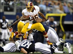 Washington Redskins running back Alfred Morris leaps over Dallas Cowboys' Dan Connor (52) as he tries to escape a tackle by Jason Hatcher, rear, in the first half today in Arlington, Texas.