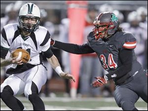 Aurora quarterback George Bollas, 11, eludes Toledo Central Catholic player Ian Butler, 34.