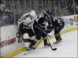 Toledo's Luke Glendening (23) and Terry Broadhurst (27) fight for control of the puck during the first period of Friday night's game against Cincinnati. At the end of the first period, the Cyclones led the Walleye, 1-0.