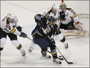 Toledo's forward Terry Broadhurst fights against two Cyclone defensemen.