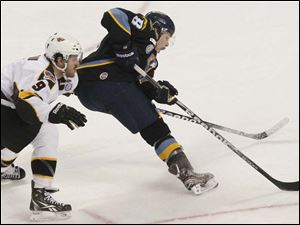 Toledo's forward Randy Rowe pushes past Cincinnati's forward Mathieu Aubin on his way to the goal during the third period. Rowe later scored the last goal of the game, though it wasn't enough to help the Walleye to victory.