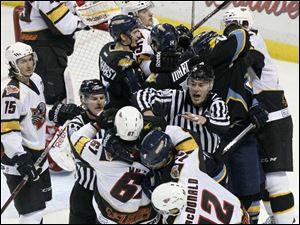 Referees attempt to separate players from the Walleye and the Cincinnati Cyclones.