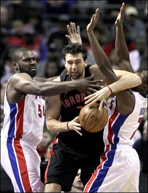 Toronto Raptors forward Andrea Bargnani, center, is pressured by Detroit Pistons forward Jason Maxiell (54) and guard Brandon Knight (7).