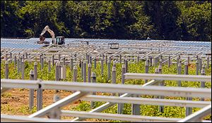 Workers install the structures which will hold solar panels on a farm in St. Paul, N.C. Land owners in rural eastern North Carolina are leasing out there land to solar companies.