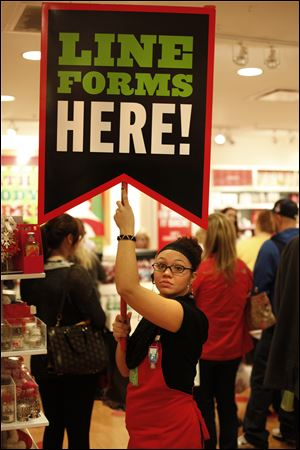 Jessica Ramirez, a salesman at Bath and Body Works, helps direct customers at Westfield Franklin Park.