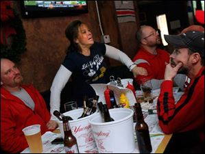 Karen Mackley, a Michigan fan, holds onto her boyfriend Scott Weber and friend Jeff Tilton, both Ohio State fans, as they watch the game at Shawn's Irish Tavern in Waterville, Ohio.