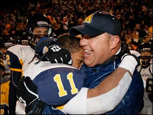 Whitmer High School player Me'Gail Frisch, 11, hugs head coach Jerry Bell after the Panthers defeat Mentor High School 62-34.