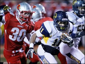 Whitmer High School player Me'Gail Frisch speeds past Mentor High School player Justin McMahon, 30, as he races to the end zone for a touchdown.