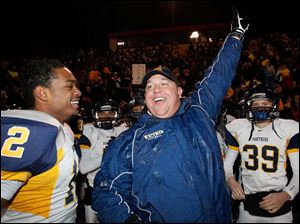 Whitmer High School head coach Jerry Bell celebrates with players Tre Sterrit, 12, and Andrew Mitchell, 39, after the win that sent them to the state championship game.
