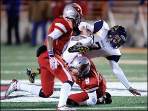 Whitmer High School quarterback Nick Holley bounces over Mentor High School player Reese Armstrong, 9, as teammate Kiyah Powell, 6, closes in.
