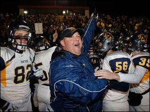 Whitmer High School head coach Jerry Bell and players Michael Dzikowski, 82, Brandon Plaza, 56, and Andrew Mitchell, 39, begin to celebrate as time expires on their 62-34 win.
