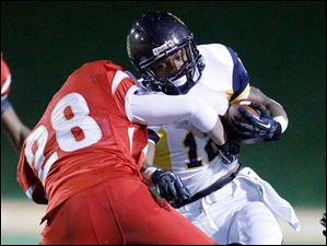 Whitmer High School player Tre Sterrit, 12, is tackled by Mentor High School player Jo Iafelice, 28.