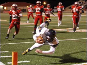 Whitmer High School quarterback Nick Holley, 7, dives into the end zone. Holley rushed for 249 yards on 27 carries in the game.