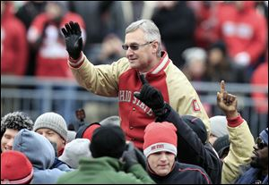 Former Ohio State coach Jim Tressel is carried on the shoulders of his 2002 national champions