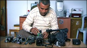 Co-director Emad Burnat displays his five broken cameras, from the documentary '5 Broken Cameras.'