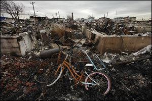 A burned bicycle lies in the ashes of a burned out home in the Breezy Point section of the Queens borough of New York.