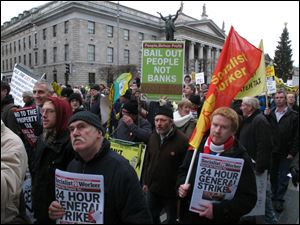 Socialist protesters march past Dublin's General Post Office today in opposition to imminent spending cuts.