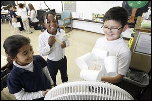 Second graders Selena Garcia, left, and Heaven Williams, center, and Ruben Angel, right, use an anemometer and a fan to collect data so that they can predict weather for a lesson.