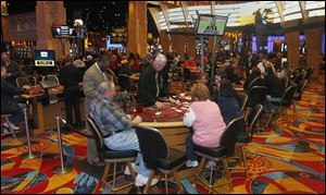 Bowling Green resident Mark Herzig deals blackjack at the casino, which features 2,037 slot machines, 80 table games, and 4 restaurants.