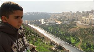 Emad's son Gibreel looks over the Israeli-built wall at Israeli settlements.  The scene is from the documentary to be shown at the St. Francis Convent Campus in Tiffin on Dec. 1.