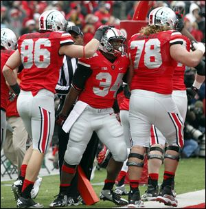 Ohio State TB Carlos Hyde (34) celebrates scoring a touchdown against  Michigan with Jeff Heuerman (86) and Andrew Norwell (78) during the first quarter Saturday, in Columbus, Ohio.
