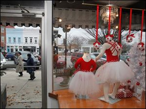 Shoppers walk outside past by Dancer's Pointe in Perrysburg Saturday.