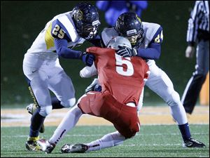 Whitmer players Austin Bly, 25, and Marcus Elliott, 24, stop Mentor's Connor Krizancic, 5, on fourth and long during the second quarter.