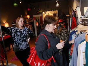 The Pink Door Boutique owner Shannon Scully, left, talks with Kate Theise, of Sylvania, right, while the latter browses the store's selection.