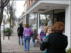 Patricia Agnolin of Windsor holds her granddaughter, Lilla Mossing, 4, as the pair follow Agnolin's daughters from shop to shop on Small Business Saturday in downtown Sylvania. Lilla got a new purse during the family's shopping trip.