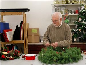 Master designer Keith Brooks works on a wreath for a client at Brooks Florist Saturday.