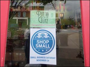 A sign on the front door of Puttin' on the Glitz store in Perrysburg encourages consumers to shop at small businesses on Saturday, Nov. 24.