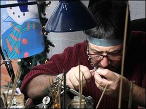 Jewelry maker Steven Kaminsky works on a piece at his Artforms glass and jewelry gallery in Perrysburg.