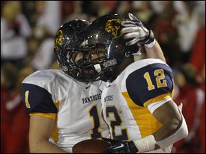 Whitmer players Devin Thomas, 1, and Tre Sterrit, 12, celebrate Sterrit's touchdown against Mentor.