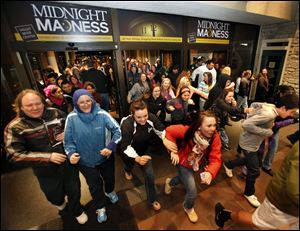 Black Friday shoppers pour into the Valley River Center mall for the Midnight Madness sale, in Eugene, Ore. All told, a record 247 million shoppers visited stores and Web sites over the four-day weekend starting Thanks