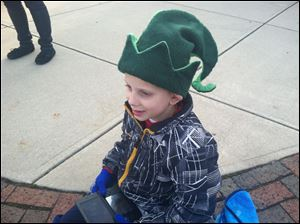 R.J. Otto, 8, of Perrysburg wears an elf hat Sunday as he watches his hometown's parade.