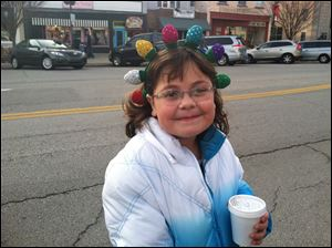 Aubrey Hill of Perrysburg stays warm with hot chocolate as she waits for the Home for the Holidays parade to begin Sunday in downtown Perrysburg.