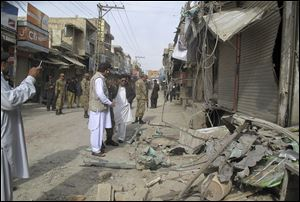 Pakistani security officials check the site of a bomb blast as the minority Muslim Shia sect observes the annual Ashoura holiday in Dera Ismail Khan, Pakistan, Sunday.