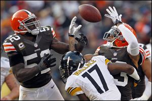 Cleveland Browns linebacker D'Qwell Jackson, left, and cornerback Joe Haden, right, break up a pass to Pittsburgh Steelers wide receiver Mike Wallace in the fourth quarter Sunday in Cleveland. The tipped ball was recovered by Browns defensive tackle Billy Winn. The Browns won 20-14.