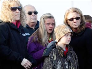 Karri Waters, left, an aunt, McKenna Shaffer, center left, a cousin, Mason Shaffer, center right, and Kristy Shaffer, right, console each other during a ceremony to remember Andrew, Alexander, and Tanner Skelton.
