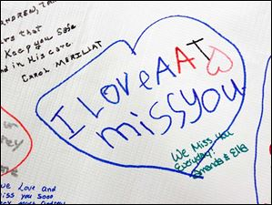 A note written on a poster at the ceremony displays love for the missing boys.