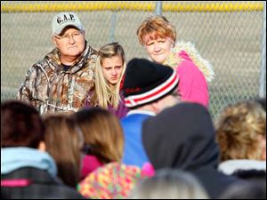 A large crowd gathers around Don Zuvers, left, the boy's grandfather, McKenna Shaffer, the boy's cousin and Tanya Zuvers, right, the boy's mother during a ceremony to remember Andrew, Alexander, and Tanner Skelton.