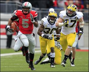 Ohio State quarterback Braxton Miller, left, breaks away from Michigan defenders Thomas Gordon, center, and Jake Ryan during the third quarter of an NCAA college football game in Columbus, Ohio. Ohio State beat Michigan 26-21.